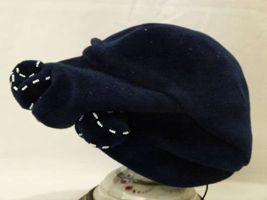 "016/022 Women's hat. Royal blue felted toque with molded crown and draped look molded brim wider at the front. Blue felt knotted bow edged with small white beads decorates the left centre of the brim at the front. Label reads ""Irene Wiener Original Model"" . No lining just black grosgrain lining trim."