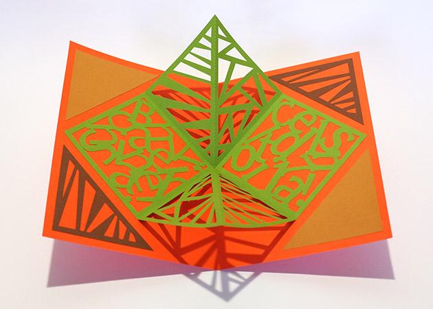 Carré plié d'anniversaire personnalisé, motifs triangles, fond orange. Vue de dessus