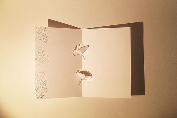 Carte en kirigami, motif Ginkgos avec frise dessinée, vue de dessus