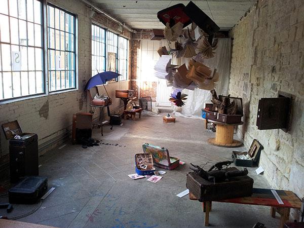 """Exposition """"Qu'est-ce qu'on trimballe, Valises d'artistes"""", par la Cie L'Emporte Pièces. Vue d'ensemble. Anis Gras – Le lieu."""