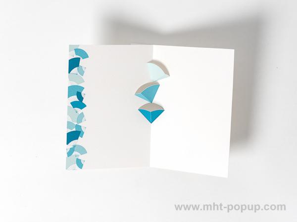 Carte en kirigami, motif Eventails avec frise dessinée couleur bleue. Intérieur de la carte vu de dessus