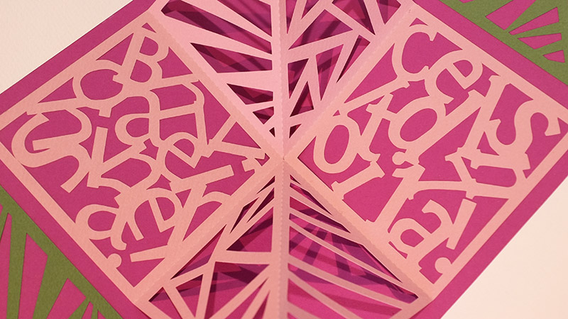 Carré plié d'anniversaire personnalisé avec motifs triangles sur fond fuschia. Détail des motifs en dentelle