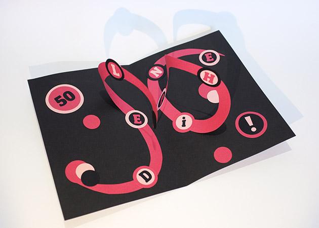Carte pop-up personnalisée d'anniversaire avec 2 spirales combinées et motifs à pois et ruban haute couture. Vue de dessus en biais
