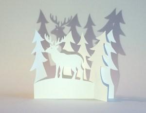 Carte de vœux en papier découpé motif Cerf et sapins, vue pliée de face