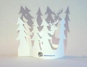 Carte de vœux en papier découpé motif Cerf et sapins, vue pliée de dos