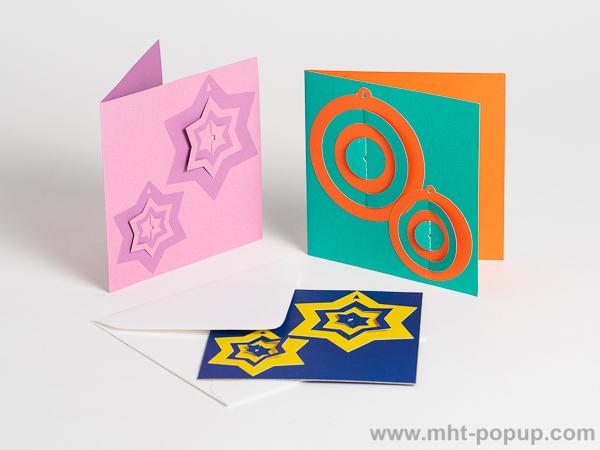 Carte de vœux en papier découpé bicolore, motifs boules et étoiles, 3 versions rose-mauve, bleu-jaune et vert-orange de face, avec enveloppe
