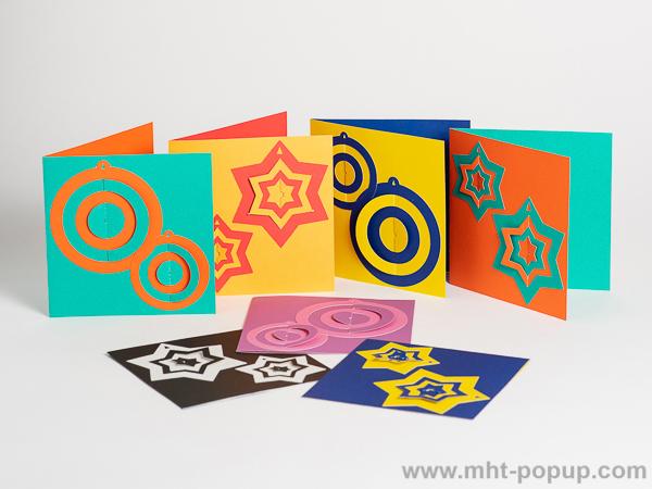 Carte de vœux en papier découpé bicolore, motifs boules et étoiles, de face