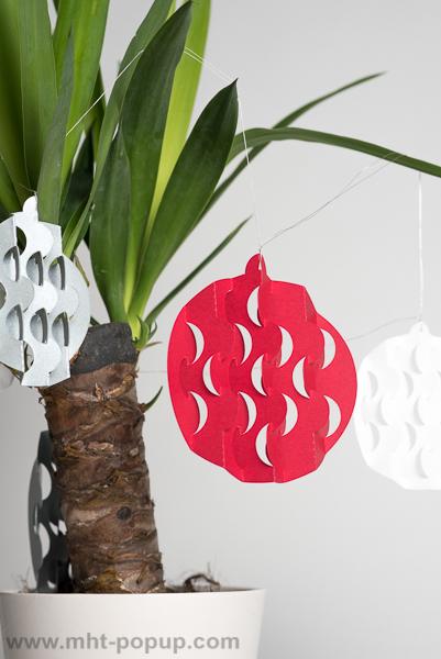Guirlande, modèle Boules psychédéliques Rouge/Blanc/Argent, disposée autour d'un yucca, détail d'une boule avec motifs découpés