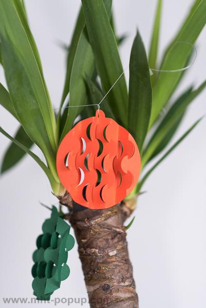 Guirlande, modèle Boules psychédéliques multicolores, disposée autour d'un yucca, détail d'une boule avec motifs découpés