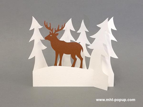 Décoration de Noël en papier découpé avec forêt de sapins et cerf. Papier blanc, or, argent et cuivre. Pliage pour créer une scène en volume