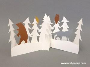 Décorations de Noël en papier découpé avec forêt de sapins, renard et ours. Papier blanc, or, argent et cuivre. Pliage pour créer une scène en volume