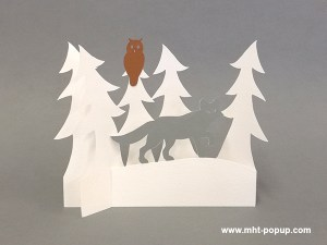 Décoration de Noël en papier découpé avec forêt de sapins et renard. Papier blanc, or, argent et cuivre. Pliage pour créer une scène en volume