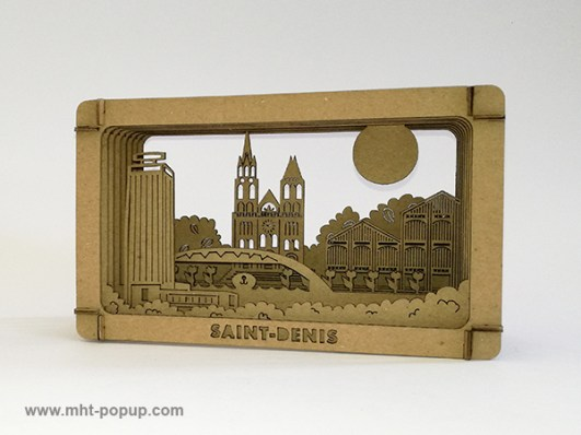 Diorama en carton brut avec éléments du patrimoine de Saint-Denis (Basilique, canal, marché, tour Pleyel…), à monter soi-même. Vue de profil gauche