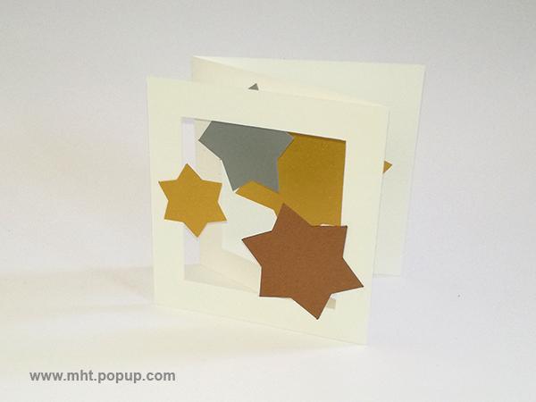 Cartes pop-up forme triptyque avec pliage en accordéon, motifs étoiles en papier or, argent et cuivre, vue de profil gauche