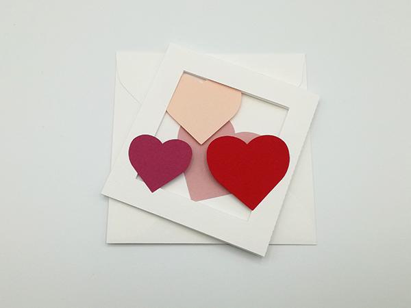 Carte avec pliage en accordéon, motifs cœurs en camaïeu rouge et rose, carte avec enveloppe