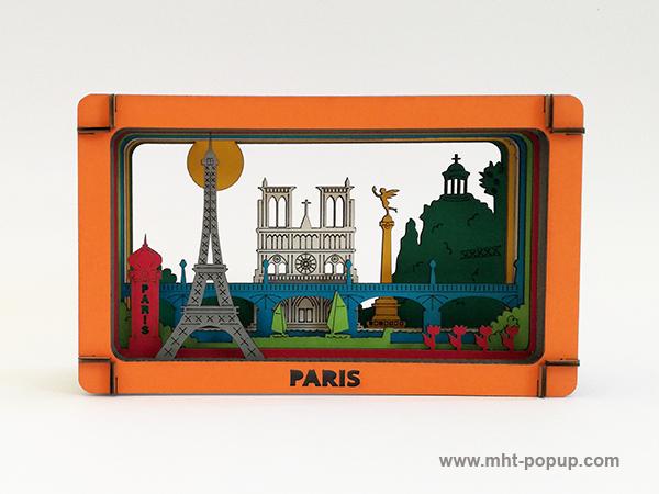Diorama en couleur avec éléments du patrimoine de Paris (Tour Eiffel, Notre Dame, Tuileries, Bastille, Buttes Chaumont, Seine, colonne Morris). Carton alvéolé recouvert de papier couleur. Gravure et découpe laser. Diorama à monter soi-même. Vue de face