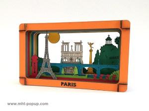 Diorama en couleur avec éléments du patrimoine de Paris (Tour Eiffel, Notre Dame, Tuileries, Bastille, Buttes Chaumont, Seine, colonne Morris), à monter soi-même. Vue de profil gauche