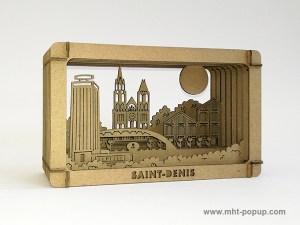 Diorama en carton brut avec éléments du patrimoine de Saint-Denis (Basilique, canal, marché, tour Pleyel…), à monter soi-même. Vue de profil droit
