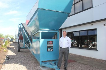 Colin Clements, Global Product Line Director beside a 1966 MK1 screening machine. This was the sixth machine built and remains a permanent feature at the front of our Dungannon Plant