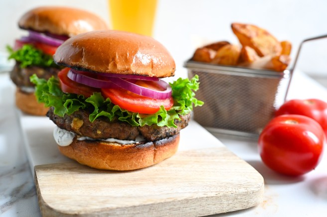 Delicious Greek-style grilled lamb burgers with feta topped with tzatziki, tomatoes, lettuce and red onions.