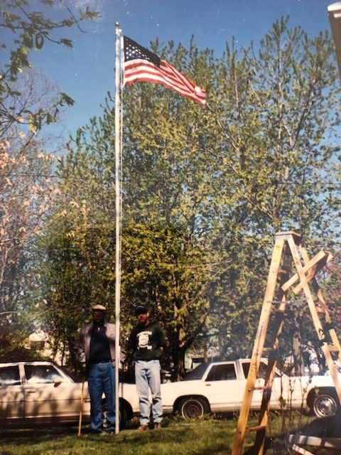 Photo of Don and Stu standing next to the newly installed flag pole with the American flag at the top