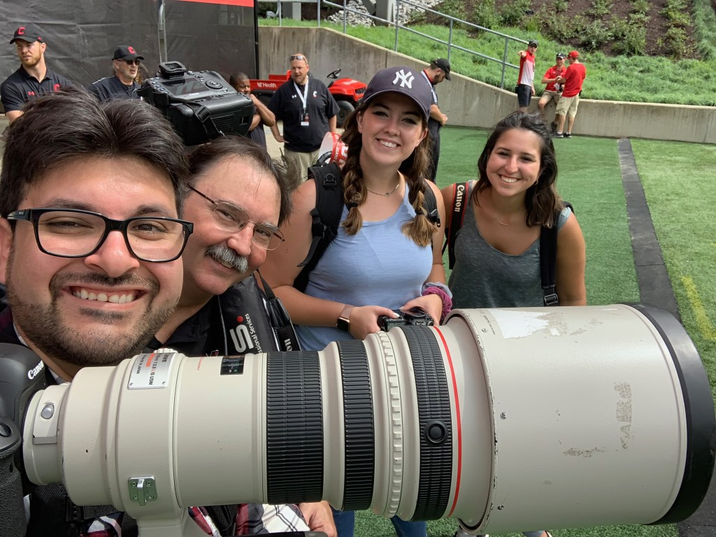 Ricardo Treviño M.S. '15 (right) at a Miami football game against University of Cincinnati with a fellow photographer and two photography students.