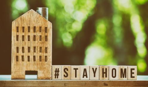 A wooden house with wooden blocks next to it and spells out #stayhome.