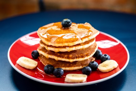 A red plate with a tower of pancakes. The pancakes are topped with blueberries and bananas.
