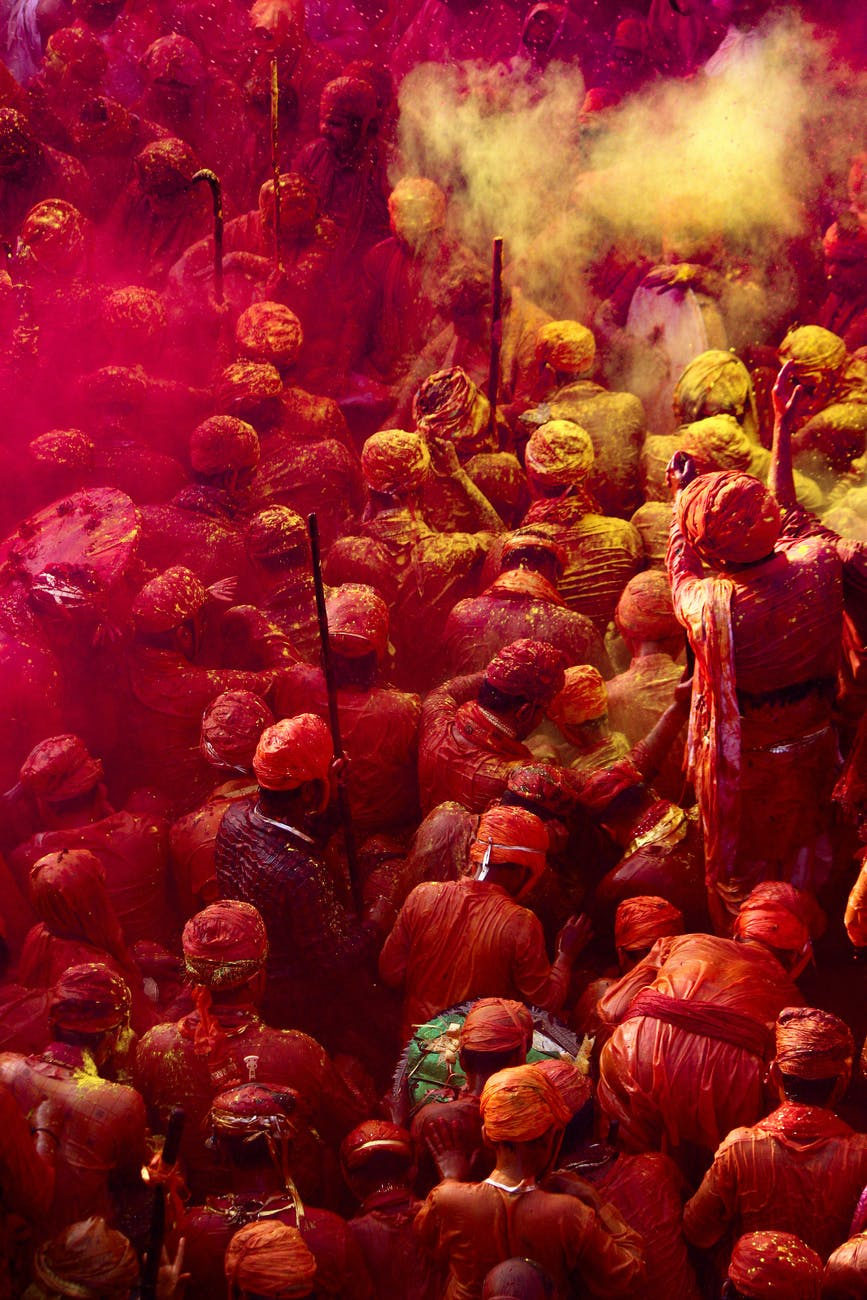 people covered with yellow and pink powder
