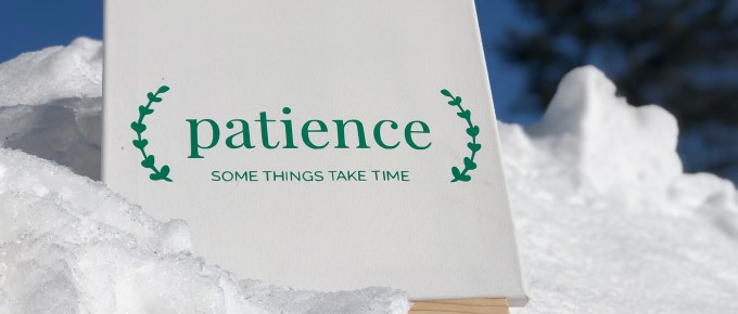 Canvas sign in the snow that says: Patience - some things take time