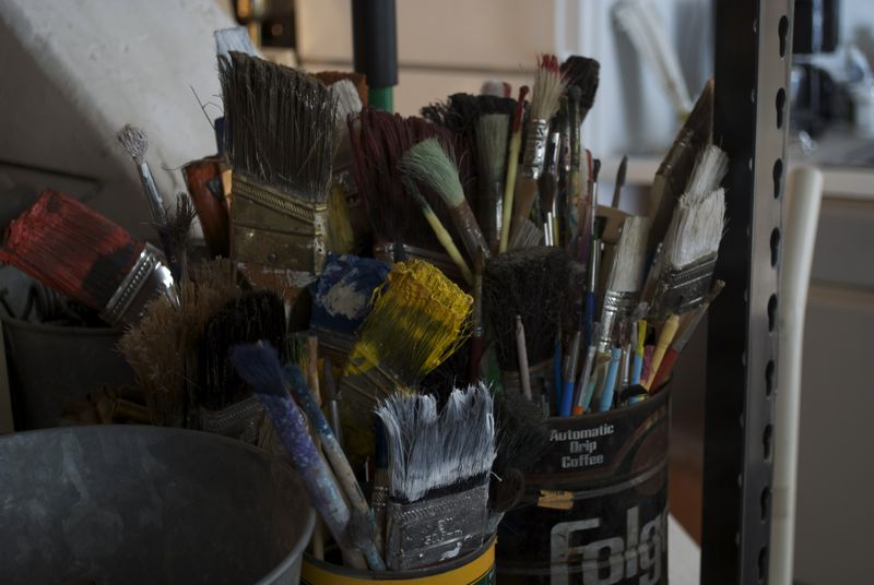 A nice bucket of used paintbrushes.