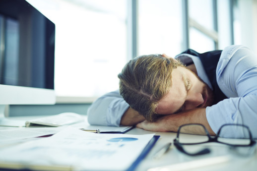 Young businessman sleeping by his desk in office