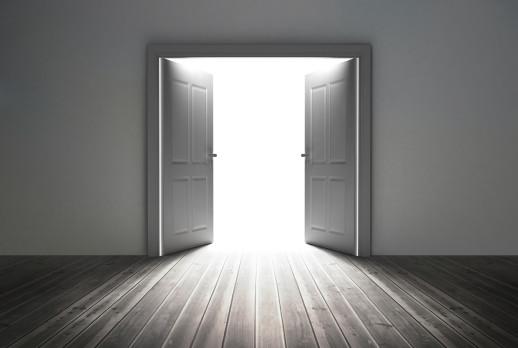 Doorway revealing bright light in dull grey room