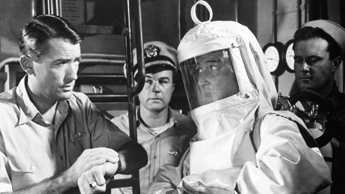 Man in nuclear suit surrounded by naval officers
