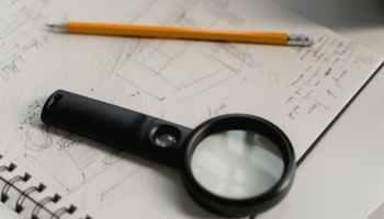 black magnifying glass beside yellow pencil