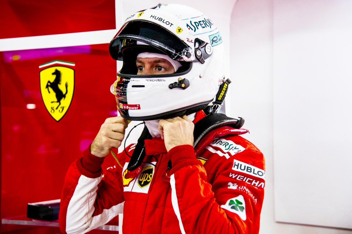 Sebastian Vettel straps up his helmet during 2018 preseason testing.