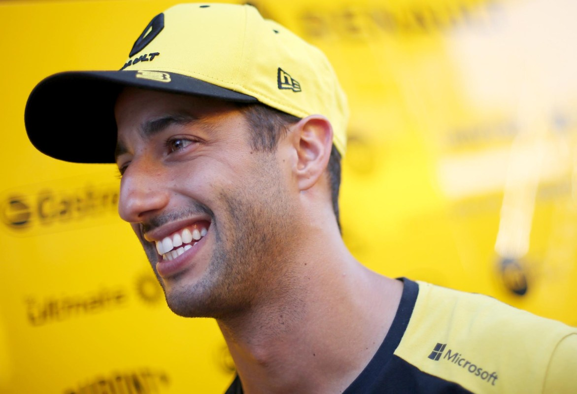 Daniel Ricciardo smiles in front of a Renault sponsor billboard at the 2019 German Grand Prix.