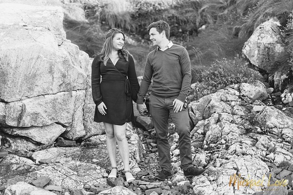 Engaged couple standing on some rocks