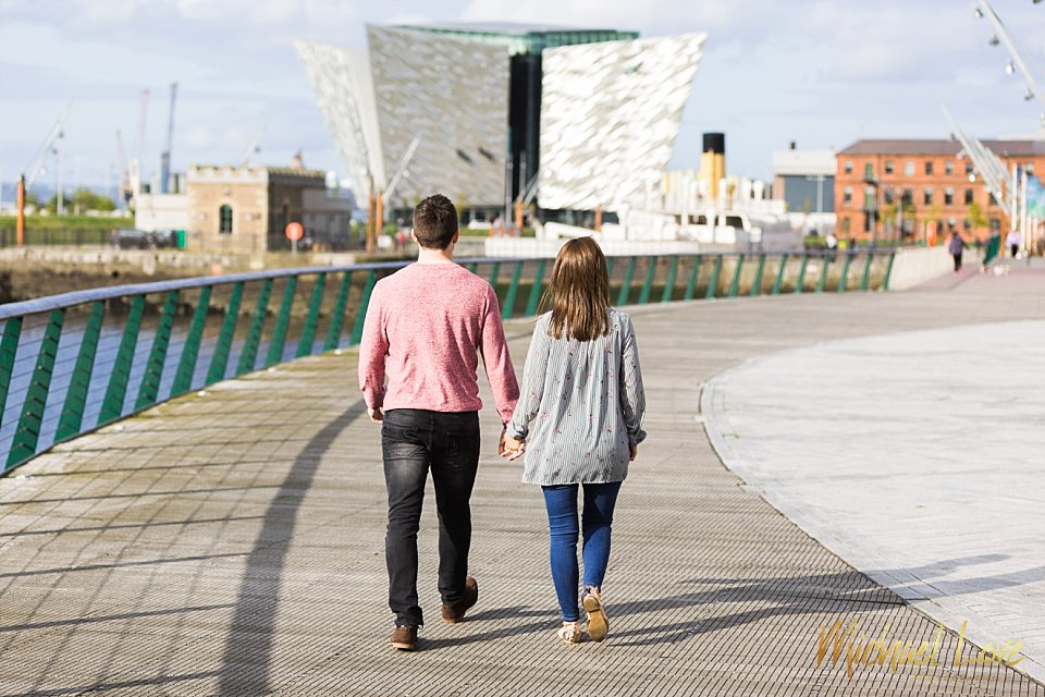 Man and woman walking in front of the Titanic building in Belfast