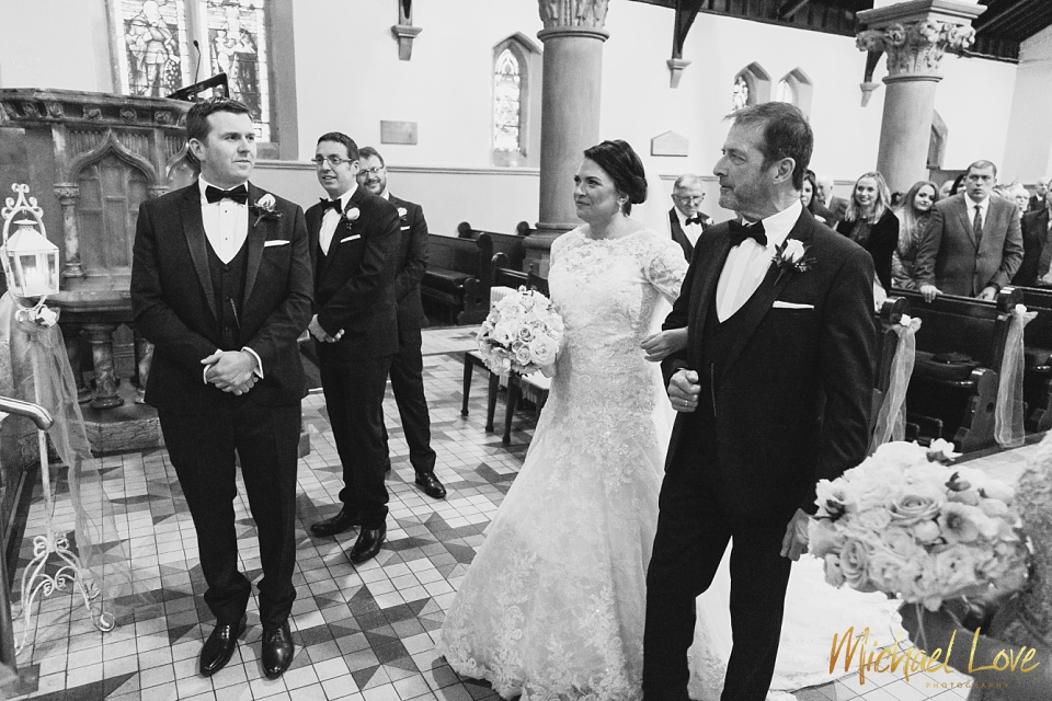 Bride meeting her groom with her father in church on her wedding day