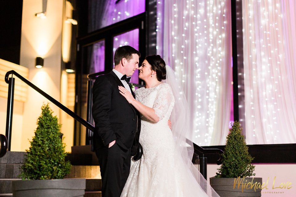 Bride and groom outside the Everglade hotel with purple fairylights