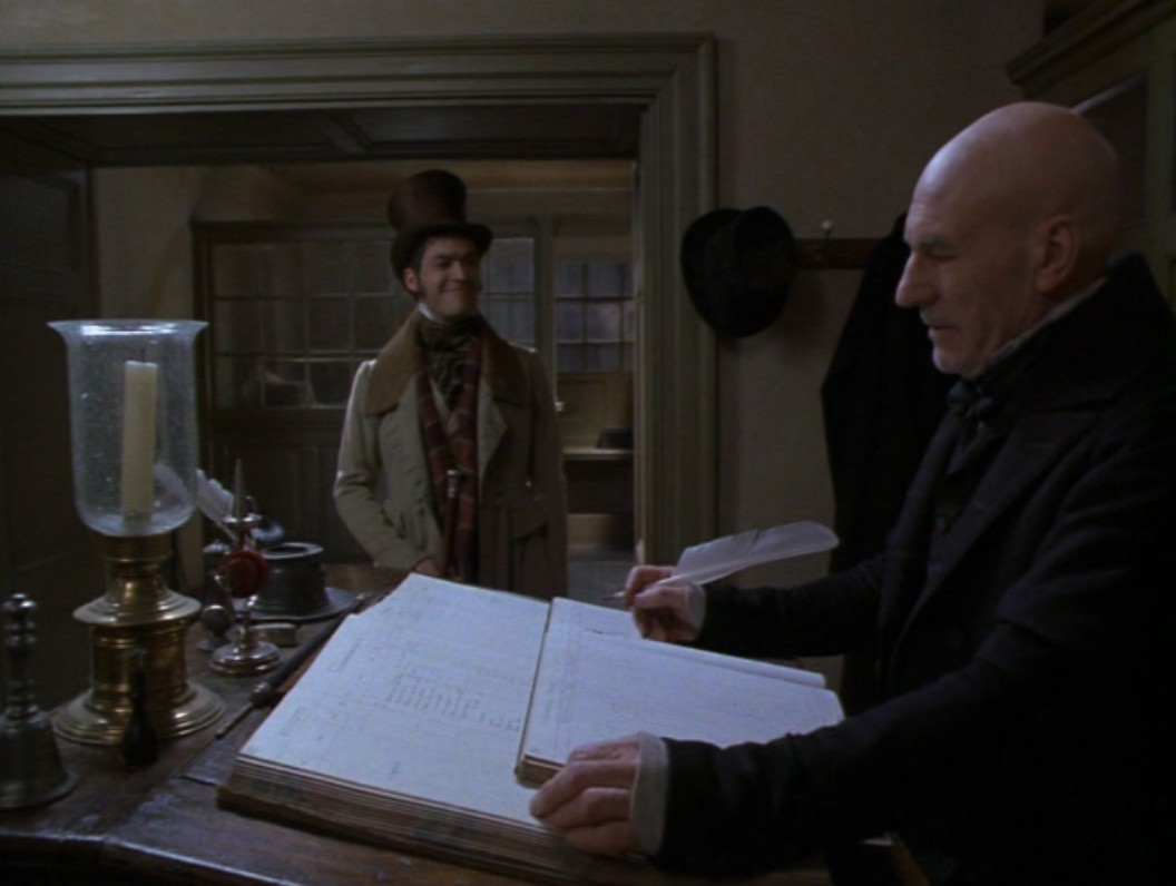 in tnts a christmas carol fred is up to no good he walks by the dirty office window peeks in at cratchit and smiles maliciously - A Christmas Carol With Patrick Stewart