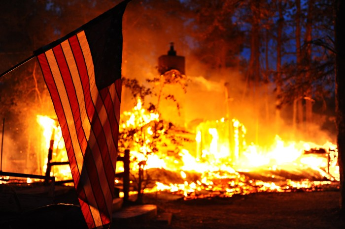 A U.S. flag hangs in front of a burning structure in Black Forest, Colo., June 12, 2013. The structure was among 360 homes that were destroyed in the first two days of the fire, which had spread to 15,000 acres by June 13. The Black Forest Fire started June 11, 2013, northeast of Colorado Springs, Colo., burning scores of homes and forcing large-scale evacuations. The Colorado National Guard and U.S. Air Force Reserve assisted in firefighting efforts. (U.S. Air Force photo by Master Sgt. Christopher DeWitt/Released)