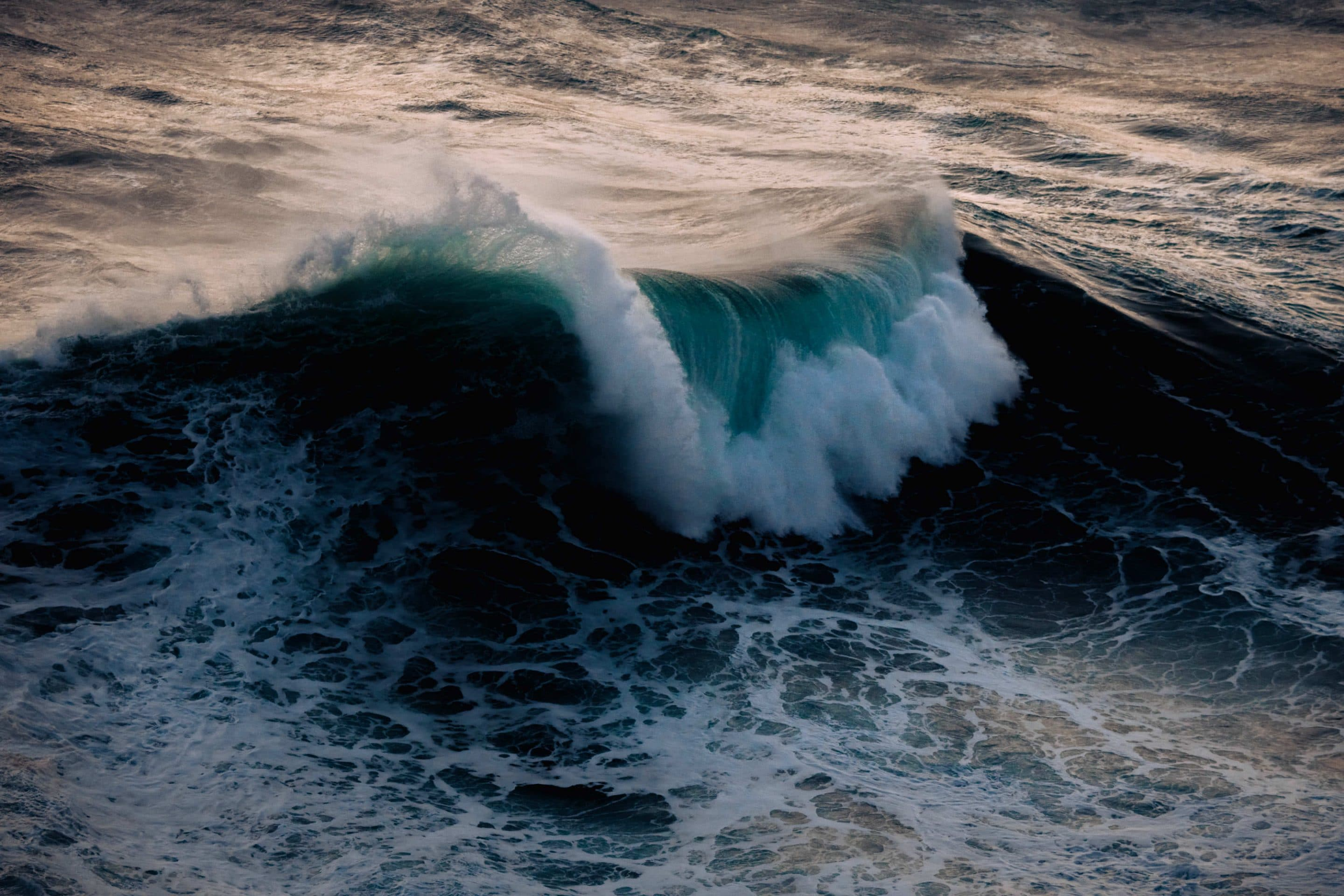 Waves crashing on the Atlantic coast at Nazaré, Portugal during a beautiful sunset by photographer Michael Schauer