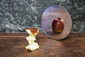 13785697 - surrealistic picture of an apple reflecting in the mirror