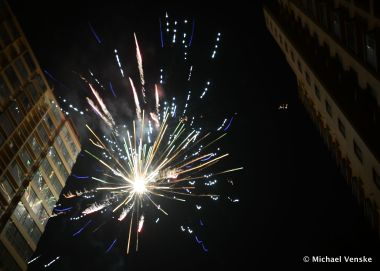Looking upward at blue and yellow fireworks exploding between tall residential Chinese buildings