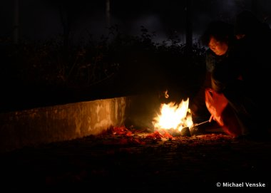 Chinese woman kneels next to small fire