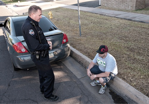 Police Question Man on Curb