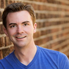 Caucasian male in blue shirt in front of a brick background