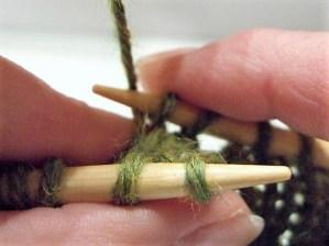 Mit der rechten Nadel die beiden gestrickten Maschen wieder aufnehmen